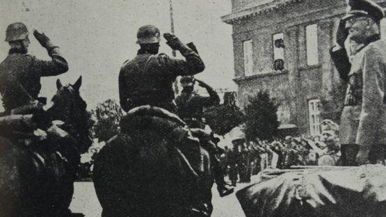 Photograph of Arthur Greiser (1897-1946), a Nazi German politician, SS-Obergruppenführer and Reichsstatthalter, saluting his troops after the Battle of Lódz, Poland. Dated 1939