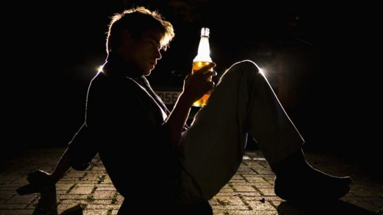 Hombre borracho con botella en vía pública