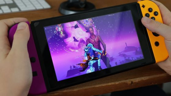 An enormous Travis Scott is seen in the video game Fortnite, standing in front of a pulsating speaker orb in the sky - the game is running on a handheld Nintendo Switch