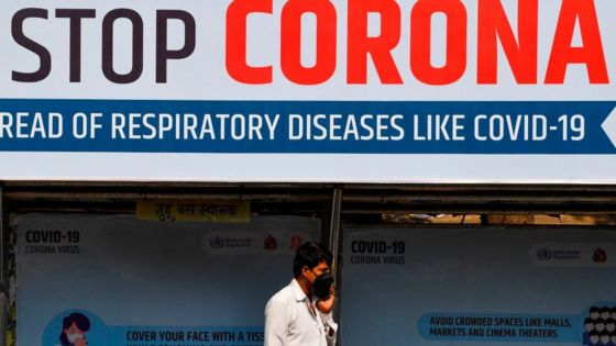 An Indian man wearing a face mask walks past a giant sign reading