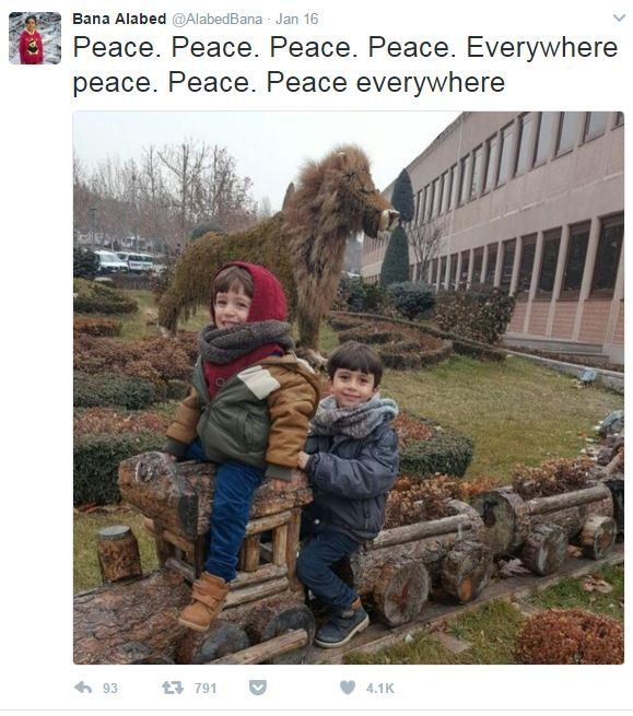 """A screenshot from the Twitter account @AlabedBana, showing her two younger brothers smiling and seated on a a row of plant pots made in the shapes of a train. The caption reads """"peace everywhere""""."""