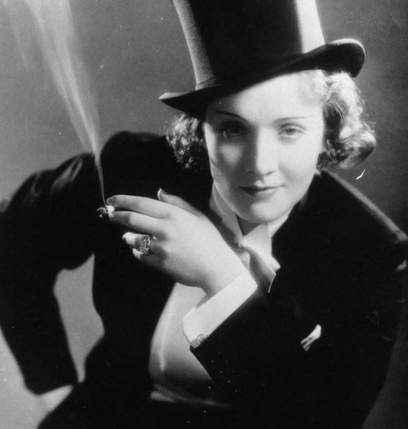 Marlene Dietrich looking to camera while dressed in a top hat and suit, smoking a cigarette