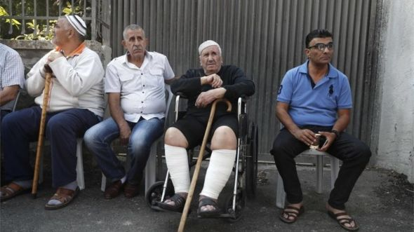 Ayoub Shamasneh (2nd right) and unidentified others outside the home in Sheikh Jarrah