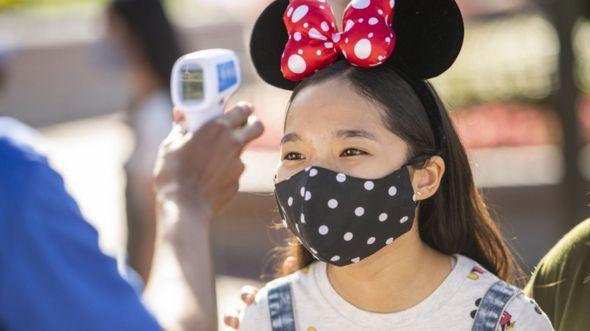 Niña con tapabocas en Disney.