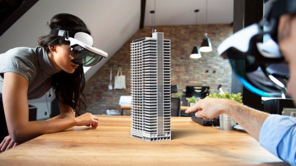 Pareja con set de realidad virtual mirando edificio