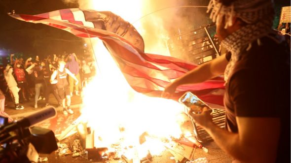 Protesters burn a US flag during a rally against the death in Minneapolis police custody of George Floyd, in Washington, DC, 31 May 2020