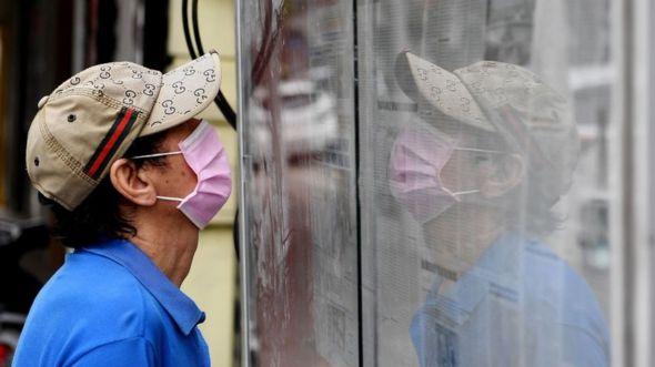 Man reading newspaper in Hanoi