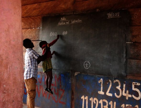 A teacher holds a child up to the blackboard