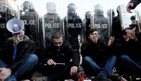 Protesters sit in puddles of red paint near anti-riot police