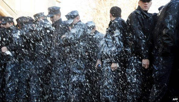 Police officers covered with milk thrown by protesting students in Pristina (7 February 2014)