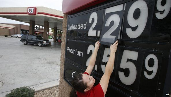 Quick Trip clerk Roxana Valverde adjusts the gas price sign numbers at a Tolleson, Ariz. QT convenience store as gas prices continue to tumble nationwide.