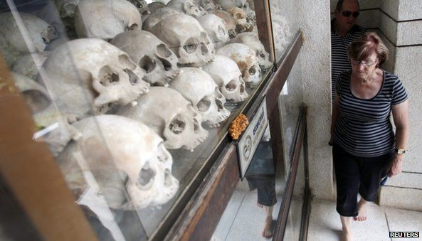 """Tourists visit at a memorial stupa with bones of more than 8,000 victims of the Khmer Rouge regime at Choeung Ek, a """"Killing Fields"""" site located on the outskirts of Phnom Penh"""