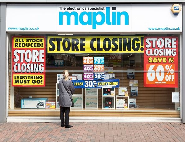 A woman looks at a store-front of Maplin's.