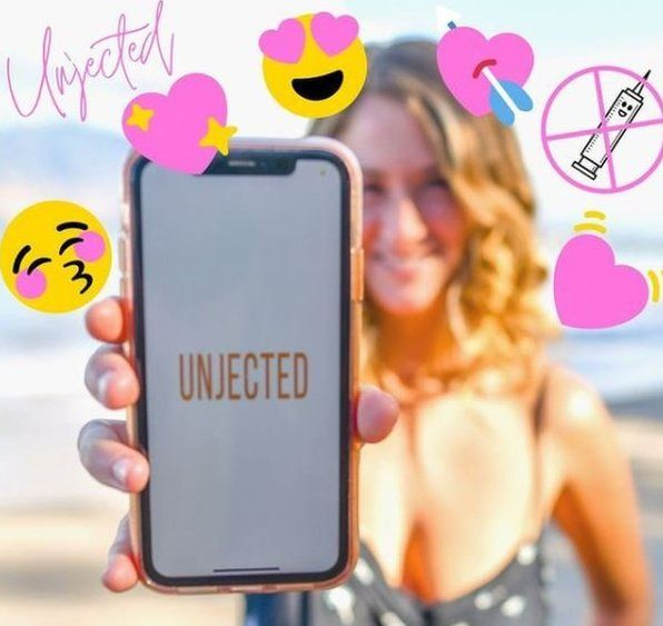 An Unjected Instagram post showing a woman on a beach holding up a mobile phone with the Unjected app on it and lots of heart emojis.