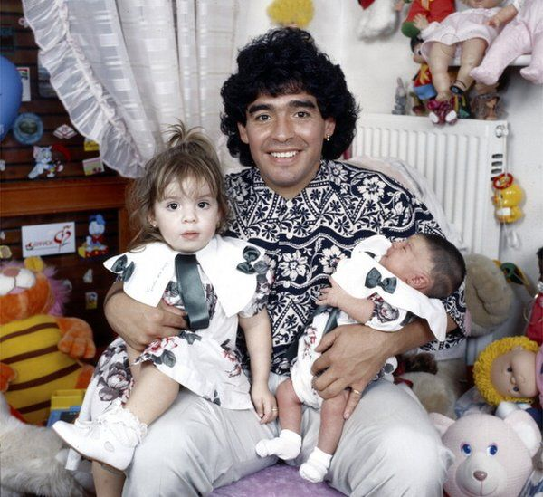 Maradona sitting in a small bedroom with his daughters Dalma e Giannina in his arms