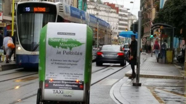 "A taxi bike in Geneva bears a poster saying ""Save the Minorities in Pakistan"""