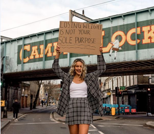 Lauren black holding a sign which says losing weight is not your sole purpose