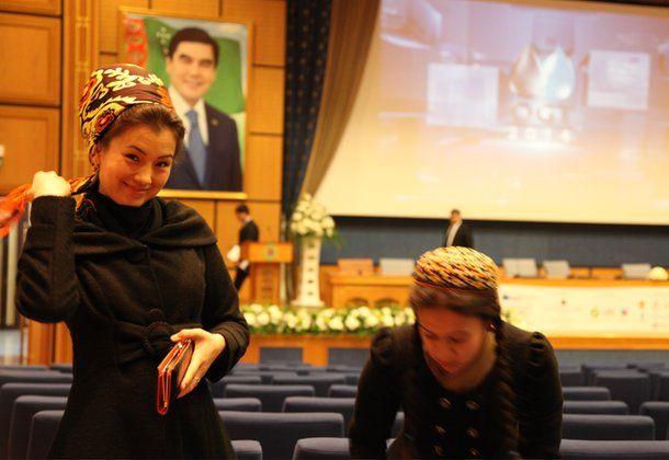 Conference volunteers with portrait of Turkmen president in the background, Ashgabat (Nov 2014)