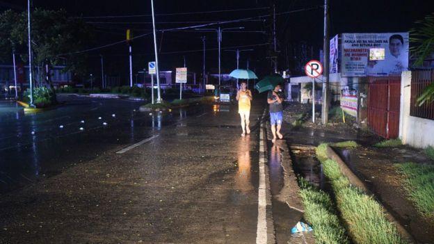 Pedestres caminham em rua deserta na cidade de Tuguegarao durante noite e segurando guardas-chuvas