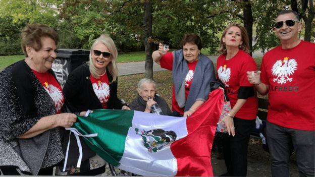 Valentina y Frania junto a familiares con una bandera mexicana.