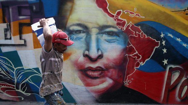 Hombre caminando en Caracas frente a un mural de Hugo Chávez.