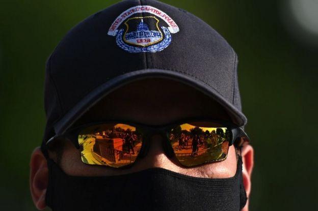 Óculos de um policial nos EUA reflete manifestantes durante um protesto em frente ao Capitólio, em Washington, DC, em 2 de junho de 2020.