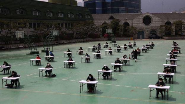 Alumnos surcoreanos dando un examen distanciados en una cancha deportiva.