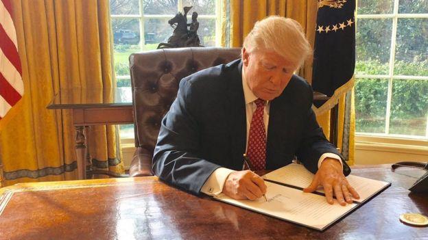 Donald Trump firma un documento