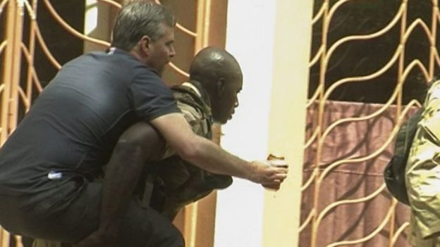 An injured rescued hostage is carried from the Radisson Hotel by security forces