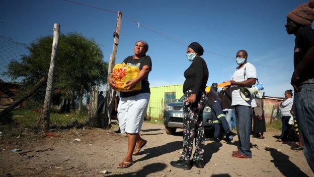 A township resident carries a food package handed out by a non governmental organisation during a 21-day nationwide lockdown aimed at limiting the spread of the coronavirus disease