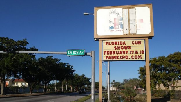 Placa anuncia feira de armas