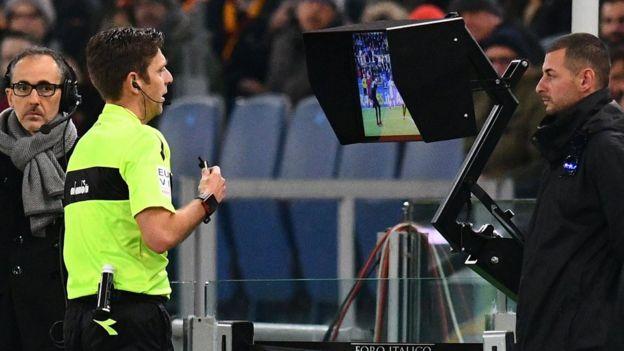 Un arbitre italien consultant la vidéo après une action litigieuse.
