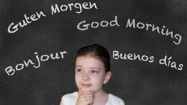 Niña con una pizarra con la palabra buen día en varios idiomas.