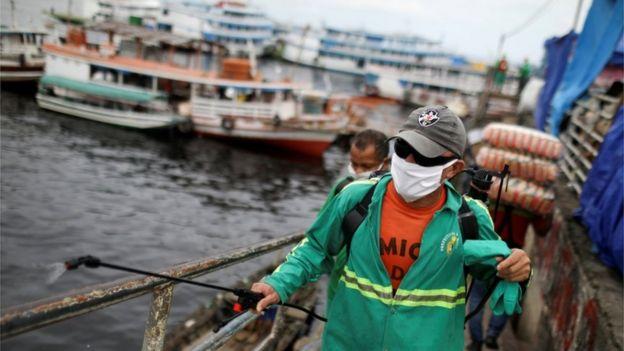 Profissional da Prefeitura desinfecta porto em Manaus