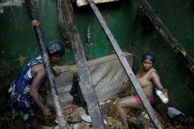 Dos mujeres recuperan sus pertenencias luego de que su vivienda quedara destruida.