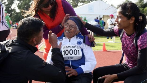 101-year-old Man Kaur of India (R) celebrates after competing in the 100m sprint in the 100+ age category at the World Masters Games at Trusts Arena in Auckland on April 24, 2017.