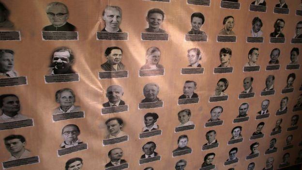 Residentes de Colonia Dignidad en pequeñas fotos carné en un cartel.