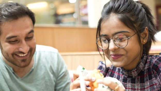 Pareja comiendo hamburguesas.