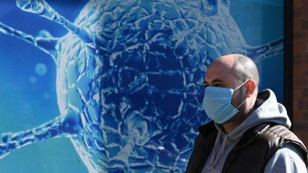 Un hombre con mascarilla caminando delante de la imagen ampliada de un virus.