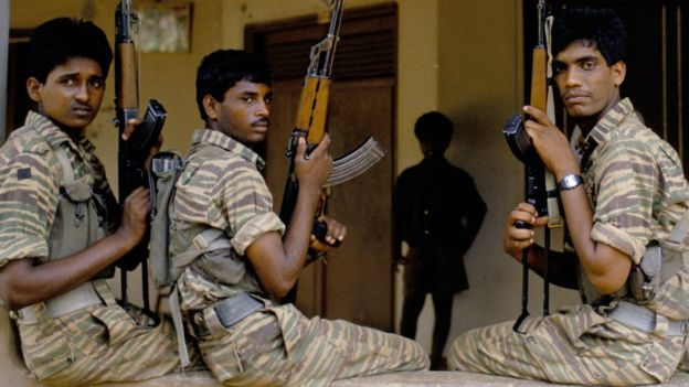 Three Tamil Tiger fighters pose in their uniform with guns