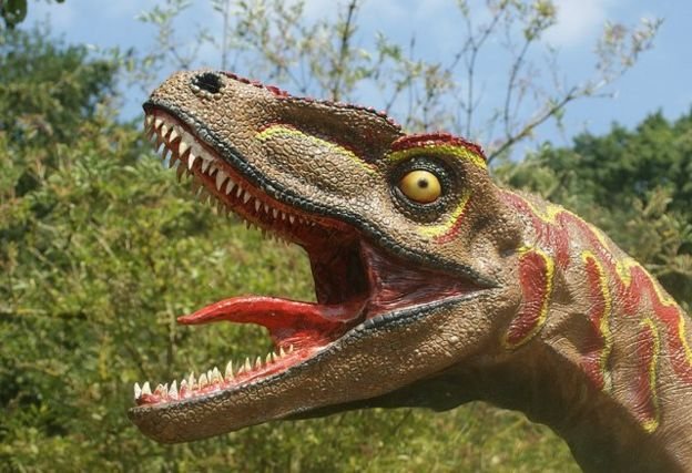 a sculpture of a dinosaur with its tongue waving wildly, a feature that is incorrect