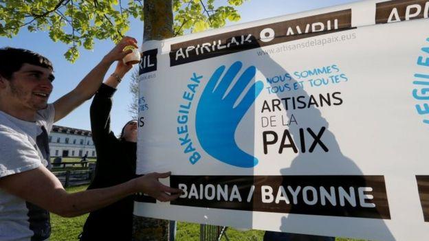 Jóvenes preparan pancartas para celebrar la entrega de armas del grupo separatista ETA, en Bayona, Francia