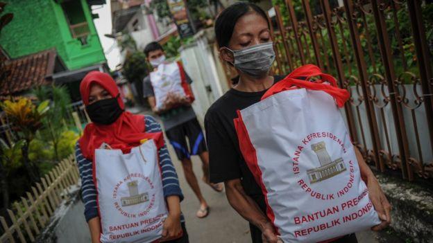 Warga membawa bingkisan berupa bantuan sosial dari Presiden di Cibeunying Kidul, Bandung, Jawa Barat, Senin (04/05).