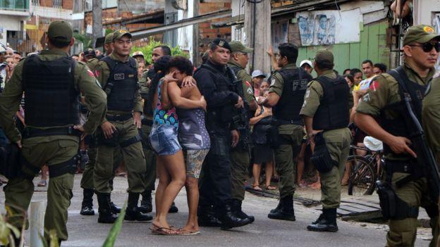 Duas mulheres abraçadas em luto, em meio a policiais, na periferia de Belém, após assassinato de 10 pessoas a tiros em um bar