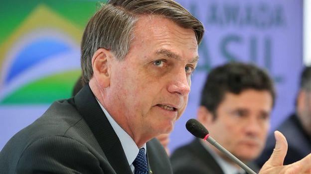 Bolsonaro fala no microfone em reunião, com Moro no plano de fundo