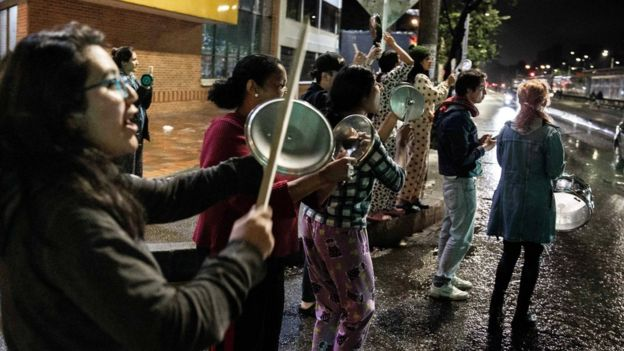 People take part in a protest with pans in Bogota