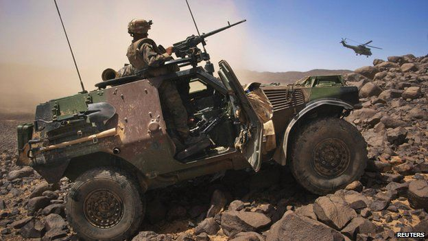 A French soldier stands guard in an armoured vehicle as a helicopter carrying French army chief Gen Bertrand Ract-Madoux gets airborne south of the nothern Malian town of Tessalit 21 March 2013.