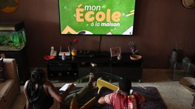 Jovens da Costa do Marfim tendo aulas pela televisão, que está sendo usada por redes estaduais e municipais do Brasil para chegar aos alunos