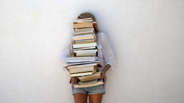 chica sosteniendo pila de libros