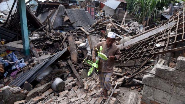 Warga mengangkat sepeda dari reruntuhan rumah yang rusak akibat gempa bumi di Lombok Barat, NTB, Senin (6/8)